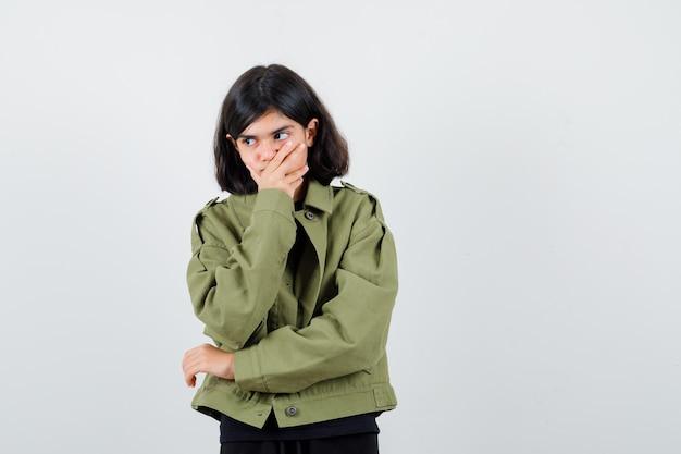 Jugendlich mädchen, das hand auf mund im t-shirt, in der grünen jacke hält und nachdenklich schaut, vorderansicht.