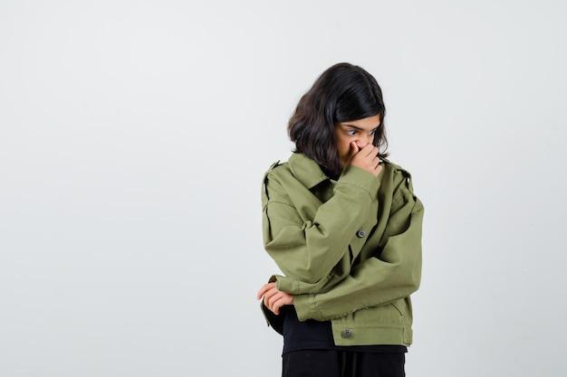Jugendlich mädchen, das hand auf mund im t-shirt, in der jacke hält und verwirrt schaut, vorderansicht.