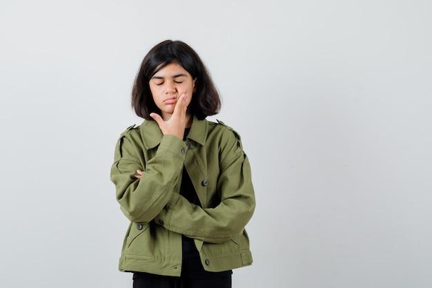 Jugendlich mädchen, das hand auf wange im t-shirt, in der grünen jacke hält und unzufrieden aussieht. vorderansicht.