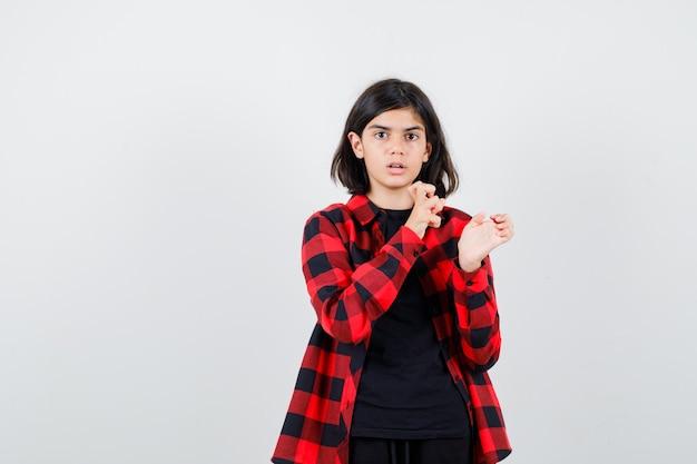 Jugendlich mädchen, das hand in verwirrter geste in lässigem hemd ausdehnt und verwirrt schaut. vorderansicht.