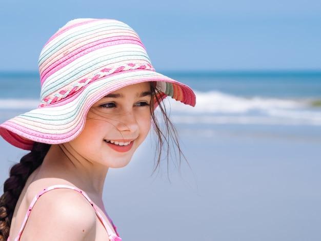 Jugendlich mädchen, das im bunten hut und im badeanzug die ansicht am tropischen strand genießt trägt.