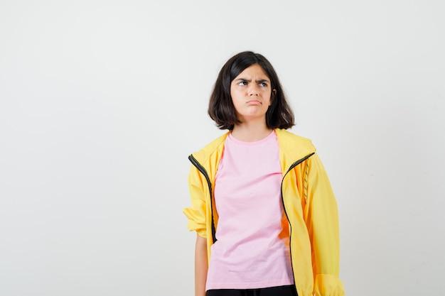 Jugendlich mädchen, das im gelben trainingsanzug, im t-shirt nach oben schaut und unzufrieden aussieht, vorderansicht.