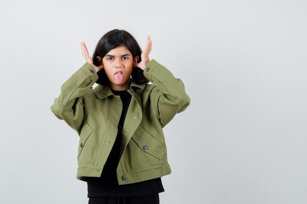 Jugendlich mädchen, das lustige geste zeigt, während sie die zunge im t-shirt, in der grünen jacke herausstreckt und amüsiert schaut. vorderansicht.