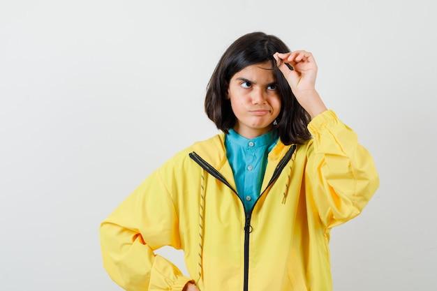 Jugendlich mädchen, das mit ihrem haar in der gelben jacke spielt und nachdenklich schaut. vorderansicht.