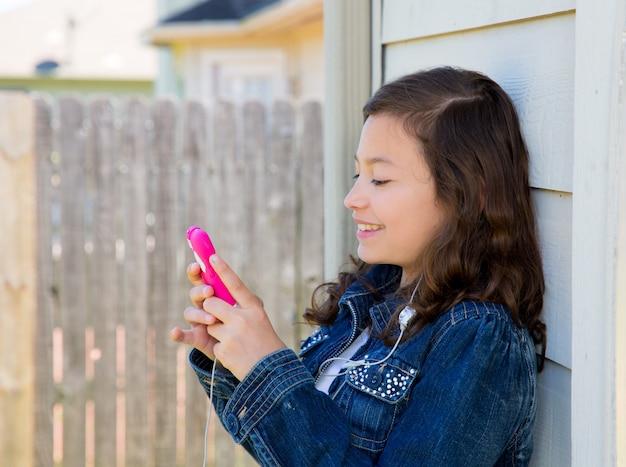 Jugendlich mädchen, das musik mit smartphone earings spielt