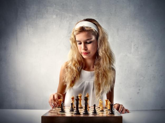 Jugendlich mädchen, das schach spielt