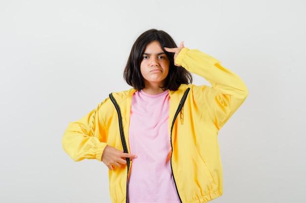 Jugendlich mädchen, das selbstmordgeste im t-shirt, in der gelben jacke macht und verärgert schaut. vorderansicht.