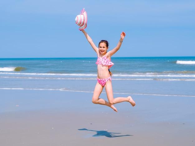Jugendlich mädchen, das spaß auf tropischem strand hat und in die luft auf der seeküste springt