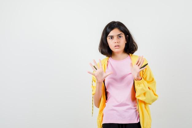 Jugendlich mädchen, das stoppgeste in gelbem trainingsanzug, t-shirt zeigt und überrascht, vorderansicht schaut.