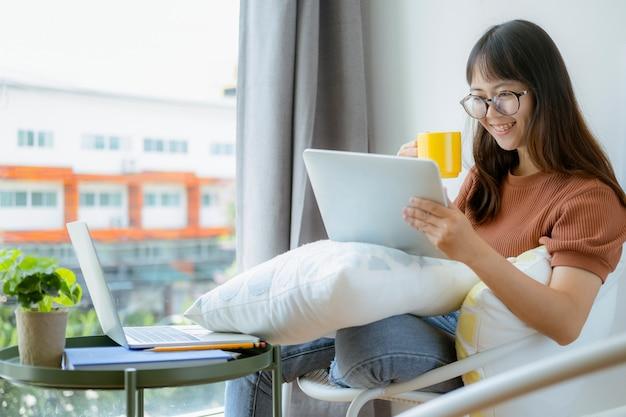 Jugendlich mädchen, das tablette verwendet und am stuhl im mitarbeitenden raumcafé sich entspannt.