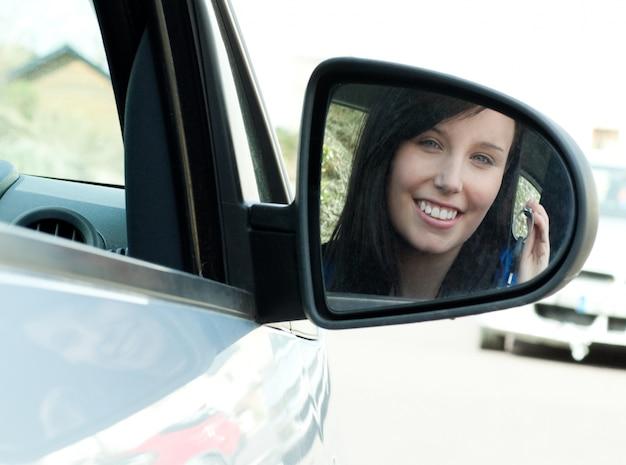 Jugendlich mädchen des brunette, das in ihrem auto hält schlüssel sitzt