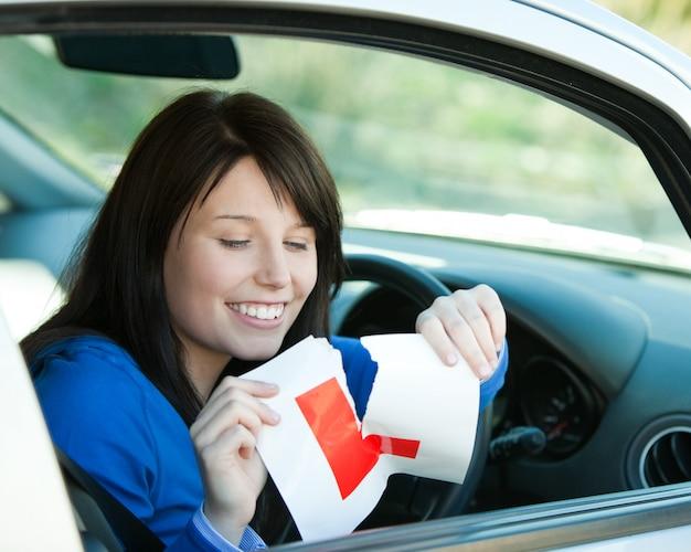 Jugendlich mädchen des brunette, das in ihrem auto reißt ein lsign sitzt