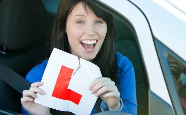 Jugendlich mädchen des glücklichen brunette, das in ihrem auto reißt ein l-zeichen sitzt