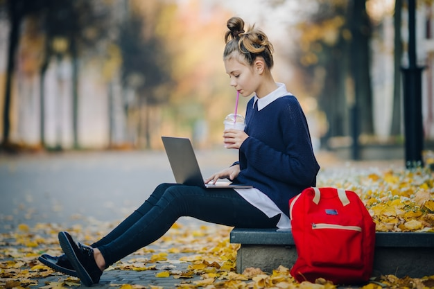 Jugendlich mädchen des hübschen hippies, das auf einem bürgersteig auf herbststadtstraße und arbeitslaptop-computer sitzt.