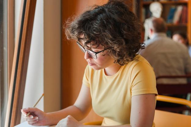 Jugendlich mädchen in den gläsern nahe fenster studierend