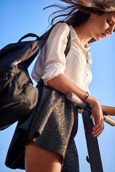 Jugendlich mädchen mit dem rucksack, rock und hemd, die den elektroroller reiten
