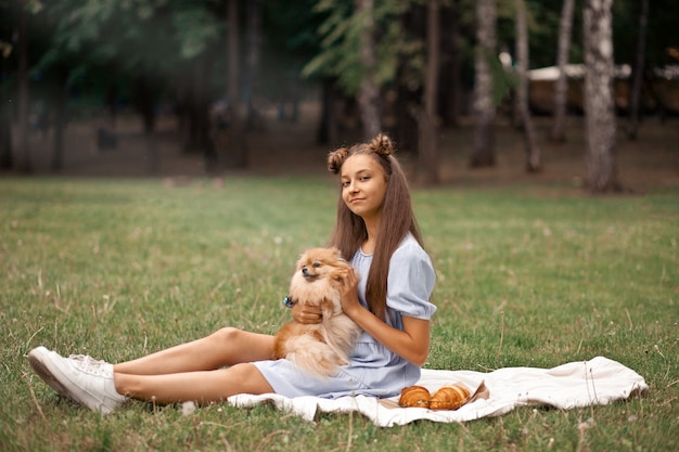 Jugendlich mädchen mit kleinem hund des haustiertiers auf einem picknick im freien.