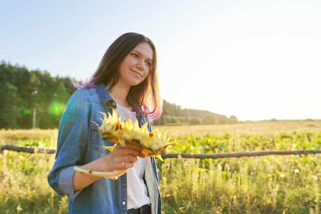 Jugendlich mädchen mit reifer sonnenblumenpflanze. herbst natürlicher landschaftshintergrund, sonnenuntergang, goldene stunde, kopienraum