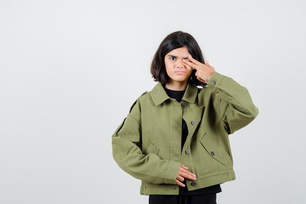 Jugendlich mädchen schließen auge mit fingern in t-shirt, jacke und schauen selbstbewusst, vorderansicht.