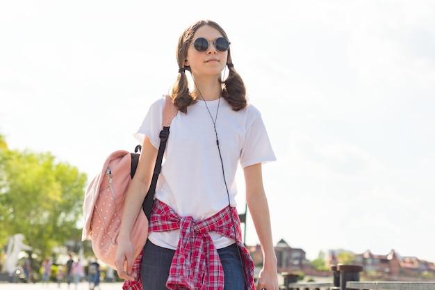 Jugendlich mädchenporträt des studenten mit dem rucksack im freien in lächelndem glücklichem gehen der straße zurück zur schule