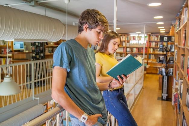 Jugendlich paare, die auf geländer und lesung sich lehnen