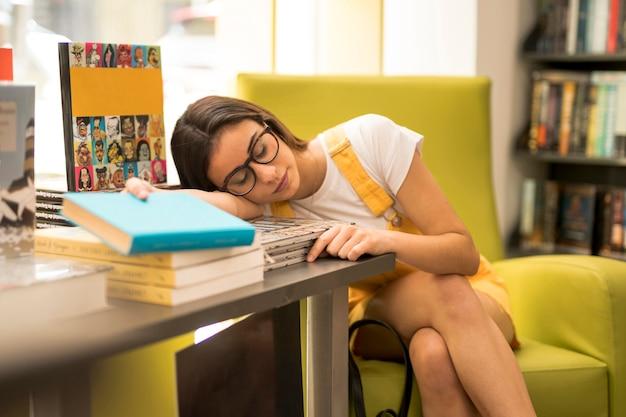 Jugendlich schulmädchen, das auf stapel büchern schläft
