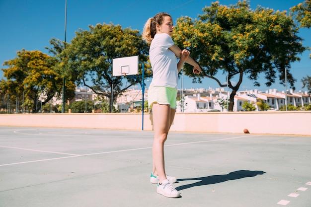 Jugendlich schulmädchen, das heraus arme am sportsground ausdehnt
