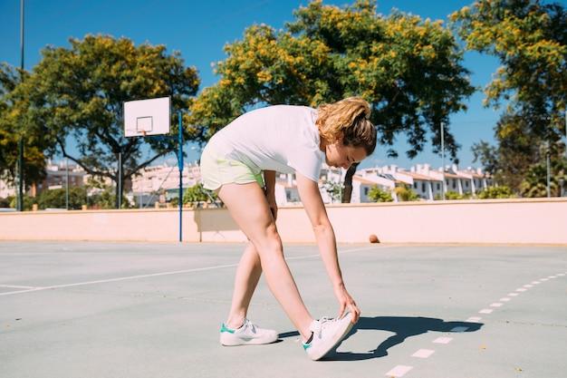 Jugendlich schulmädchen, das heraus fahrwerkbeine am sportsground ausdehnt