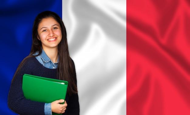 Jugendlich student, der über französischer flagge lächelt