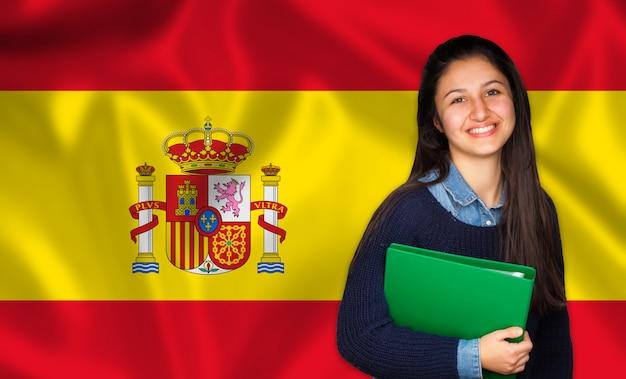 Jugendlich student, der über spanischer flagge lächelt
