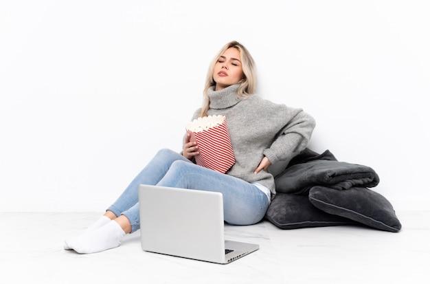 Jugendlichblondine, die popcorn beim aufpassen eines films auf dem laptop leidet unter rückenschmerzen für das haben einer bemühung essen
