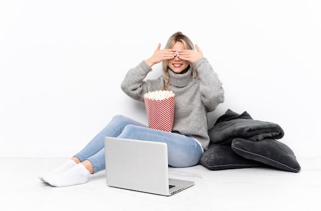 Jugendlichblondine, die popcorn beim aufpassen eines films auf der laptopbedeckung essen, mustern durch hände