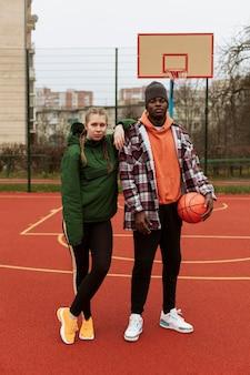 Jugendliche auf dem basketballplatz zusammen