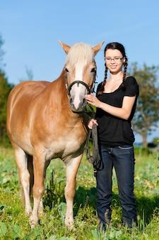 Jugendliche, die auf einer wiese im sommer mit ihrem pferd steht