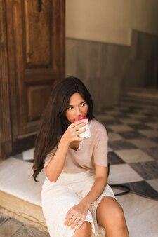 Jugendliche, die auf trinkendem kaffee der tür von der schale sitzt