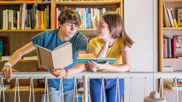 Jugendliche, die beim lesen in der bibliothek sich verständigen