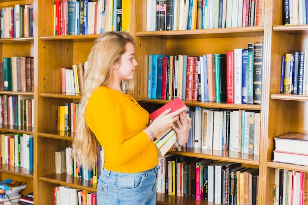 Jugendliche, die bücher vom bibliotheksregal nimmt