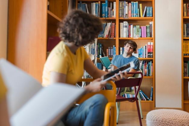 Jugendliche, die einander in der bibliothek betrachten