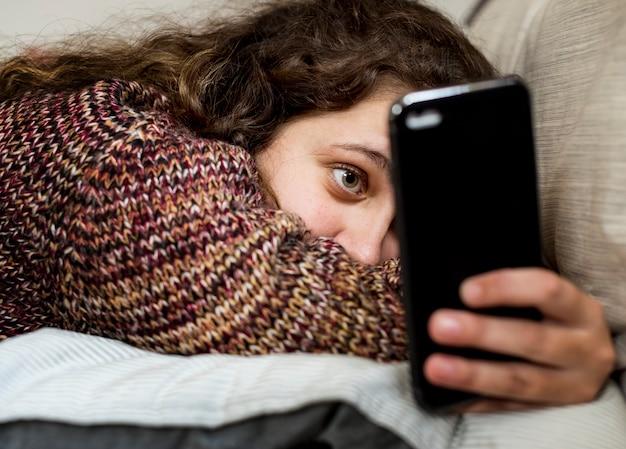 Jugendliche, die einen smartphone auf einem bett verwendet