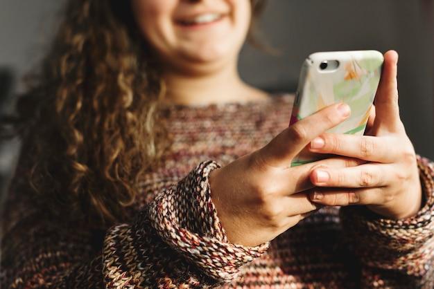 Jugendliche, die einen smartphone auf einem sozial- und neigungskonzept des betts verwendet