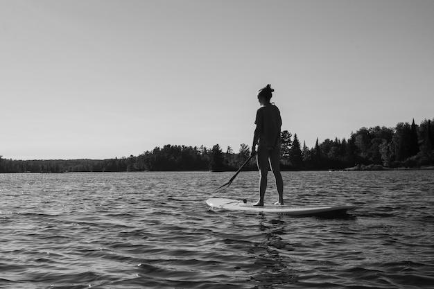 Jugendliche, die im see, see des holzes, ontario, kanada paddleboarding ist