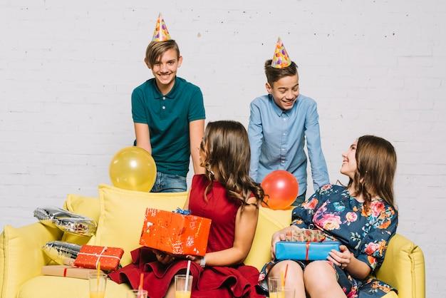 Jugendliche, die in der hand die geschenke betrachten ihre freunde tragen partyhut betrachten