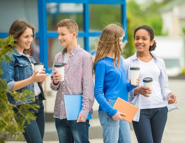 Jugendliche, die kaffee am park nach lektionen trinken.