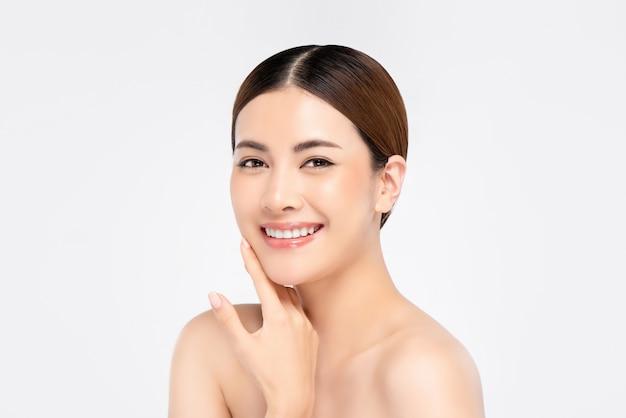 Jugendliche hübsche asiatische frau mit hand, die gesicht auf weißer wand für schönheits- und hautpflegekonzepte berührt