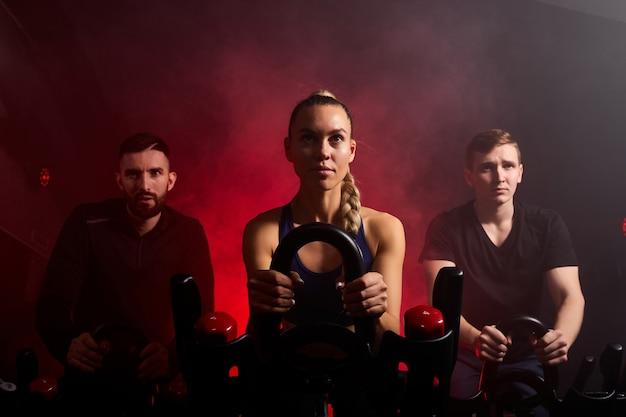 Jugendliche im fitnessstudio trainieren ihre beine beim cardio-training und haben einen spinning-kurs im fitnessstudio in einem dunklen, neonbeleuchteten, rauchigen raum