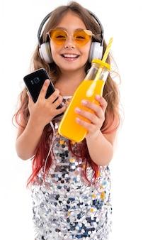 Jugendliche im funkelnden kleid und in der gelben sonnenbrille, mit großen weißen kopfhörern
