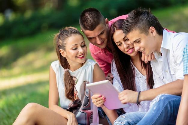 Jugendliche im park mit tablette