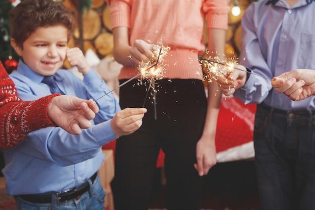 Jugendliche in festlicher weihnachtskleidung mit brennenden wunderkerzen in einem studio-interieur.