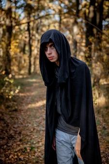 Jugendliche in halloween-kostümen im wald. halloween vampir im wald