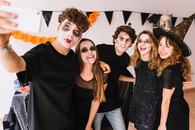 Jugendliche in halloween-kostümen machen selfie